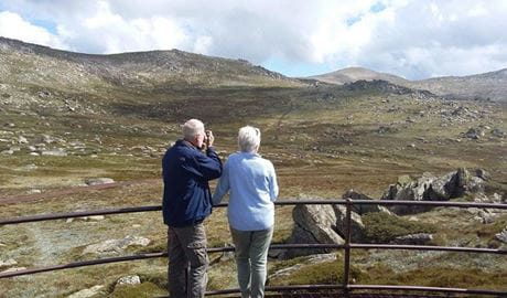 A couple take in the alpine landscape from the viewing platform of Kosciuszko lookout in Kosciuszko National Park. Photo: Luke McLachlan © DPIE