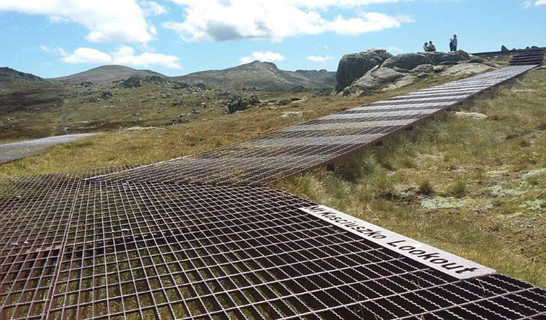 A metal mesh path heading up towards Kosciuszko lookout with mountains in the background in Kosciuszko National Park. Photo: Luke McLachlan © DPIE