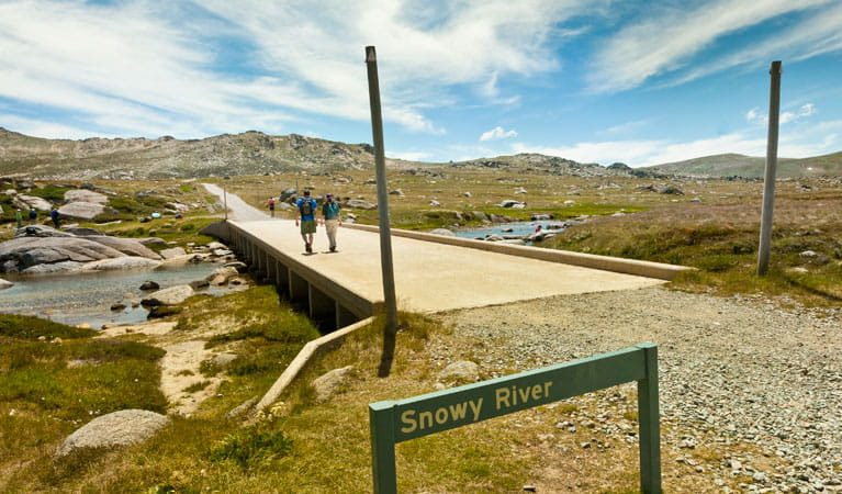 Two people cross the Snowy River along the Kosciuszko Summit trail. Photo: Murray Vanderveer