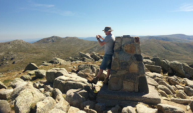 A hiker takes a photo from the summit of Mount Kosciuszko. Photo: E Sheargold/OEH