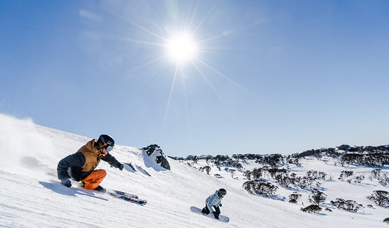 A skier and snowboarder speed down snowfields at Perisher Resort in Kosciuszko National Park. Photo: Images supplied courtesy of Perisher Ski Resort