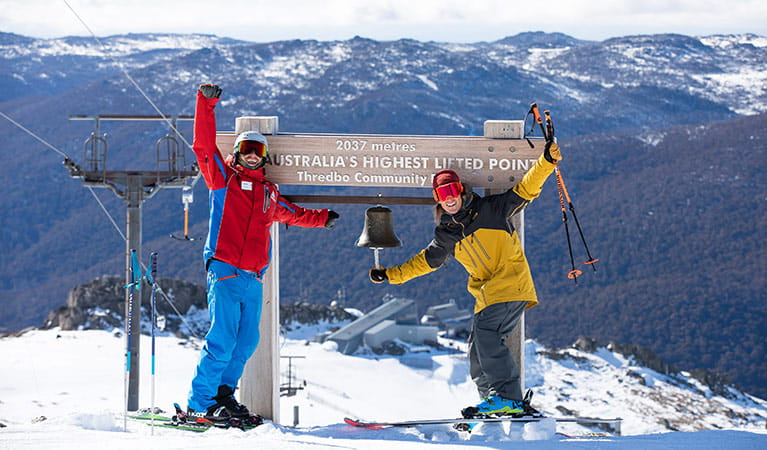 Two skiers ring the bell a Australia's highest lifted point, in Thredbo Resort. Photo: Thredbo Resort.