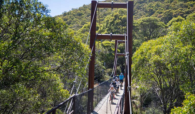 A family of mountain bike riders cycle across a suspension bridge along Thredbo Valley track, Kosciuszko National Park. Photo: Thredbo Resort