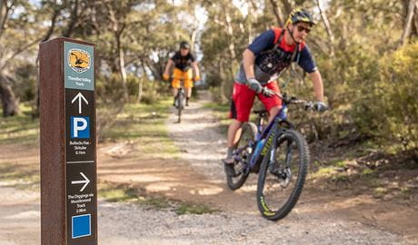 Two mountain bike riders cycle past a sign at the junction of Muzzlewood and Thredbo Valley tracks, Kosciuszko National Park. Photo: Robert Mulally/DPIE