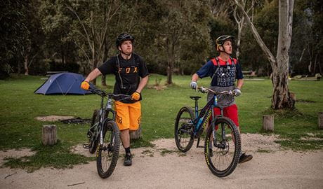 Two mountain bike riders walk past a tent at Ngarigo campground, Kosciuszko National Park. Photo: Robert Mulally/DPIE