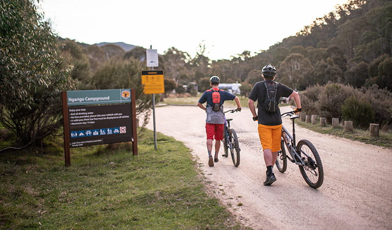 Two mountain bike riders walk past a sign entering Ngarigo campground, Kosciuszko National Park. Photo: Robert Mulally/DPIE