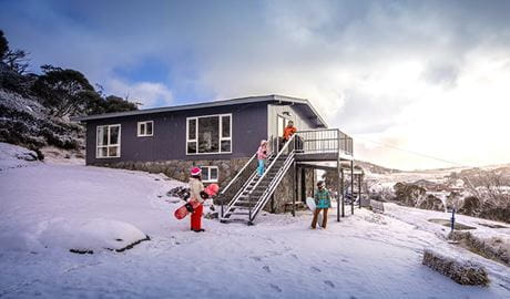 A family in the snow outside Numbananga Lodge, Kosciuszko National Park. Photo: Murray Vanderveer/OEH