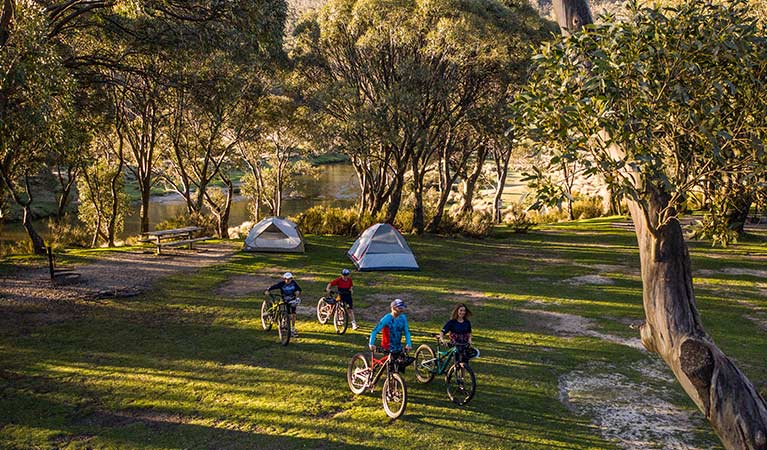 A family unloads bikes from a van and walks towards tents at Thredbo Diggings campground, Kosciuszko National Park. Photo: Robert Mulally/DPIE