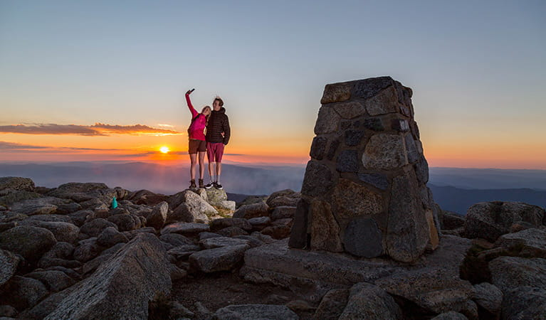 A woman and man take a selfie photo at the summit of Mount Kosciuszko at sunset, Kosciuszko National Park. Photo: Tourism Snowy Mountains
