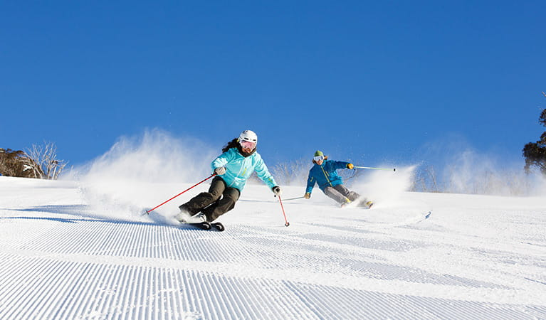 Two skiers on freshly groomed slopes at Thredbo, Kosciuszko National Park. Photo: Thredbo Resort