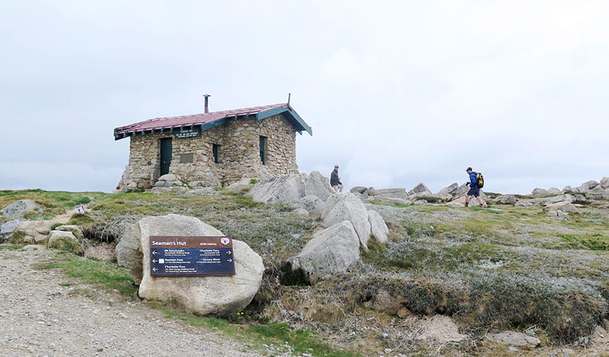 View of hikers passing historic Seamans Hut, with gravel trail and large boulders in the foreground. Photo: Stephen Townsend © DPIE