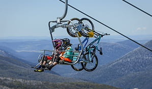 Two mountain bike riders with bikes take a chairlift to the top of Thredbo Mountain Bike Park, Kosciuszko National Park. Photo: Thredbo Resort