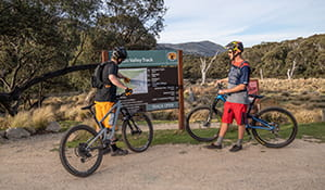 Two mountain bike riders read Thredbo Valley track signage at Thredbo Diggings campground, Kosciuszko National Park. Photo: Robert Mulally/DPIE
