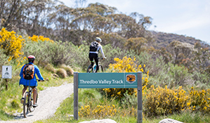 Two mountain bike riders pass a sign on Thredbo Valley track, Kosciuszko National Park. Photo: Boen Ferguson/DPIE