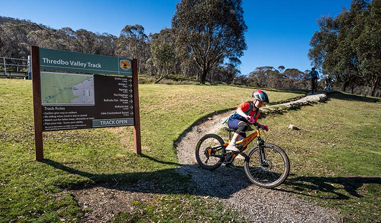 A young girl mountain bikes past a sign at the start of Thredbo Valley track, Kosciuszko National Park. Photo: Robert Mulally/DPIE