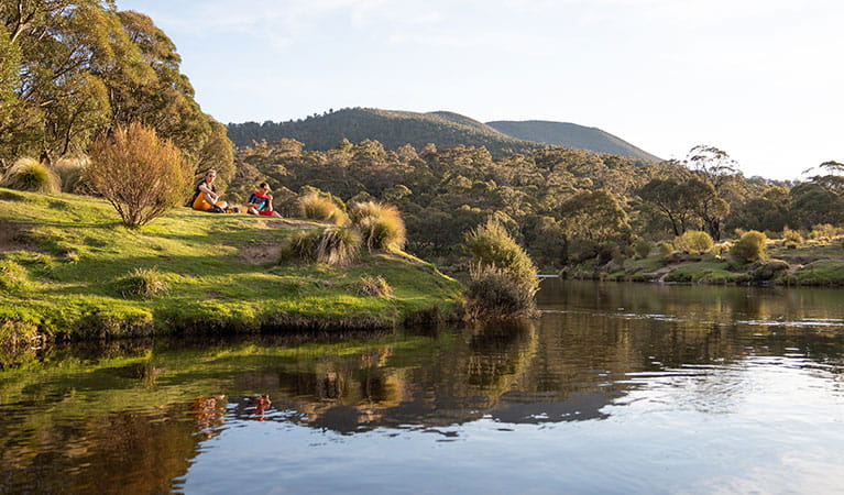 Two men sit beside the Thredbo River near Thredbo Diggings campground, Kosciuszko National Park. Photo: Robert Mulally/DPIE