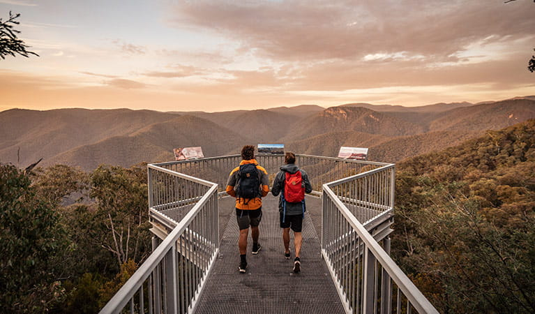 2 men walk to Black Perry lookout at sunrise, Tumut area, Kosciuszko National Park. Photo: Robert Mulally/OEH.