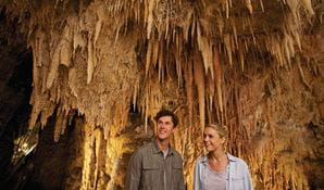 A couple tour Jillabenan Cave, Yarrangobilly Caves, Kosciuszko National Park. Photo: Destination NSW