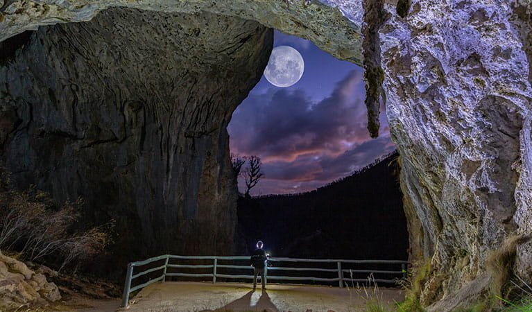 A visitor stands inside the entrance to North Glory Cave, looking out towards Kosciuszko National Park at dusk with a full moon in the sky. Photo: Adam Klumper © Adam Klumper