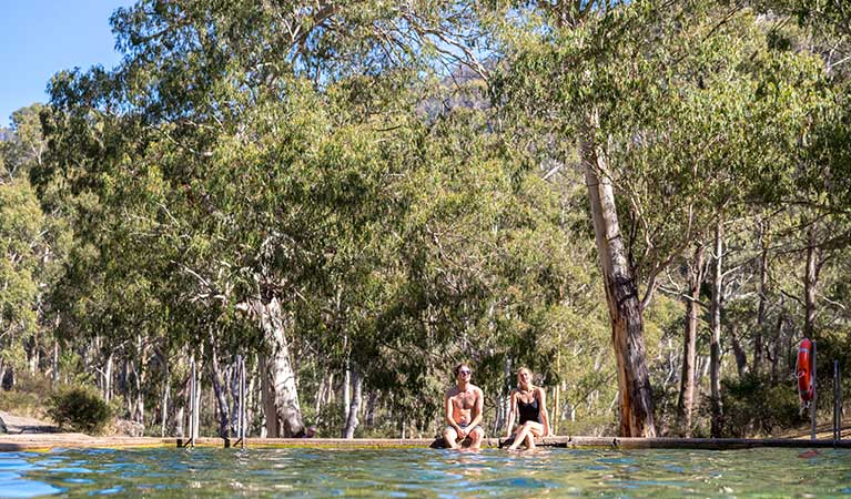 A couple sit by the thermal pool, Yarrangobilly area in Kosciuszko National Park. Photo: Boen Ferguson/OEH.
