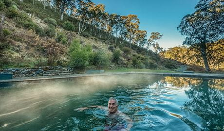 A man relaxes in the steaming waters of Yarrangobilly Caves thermal pool, in Kosciuszko National Park. Photo: Murray Vanderveer/DPIE.