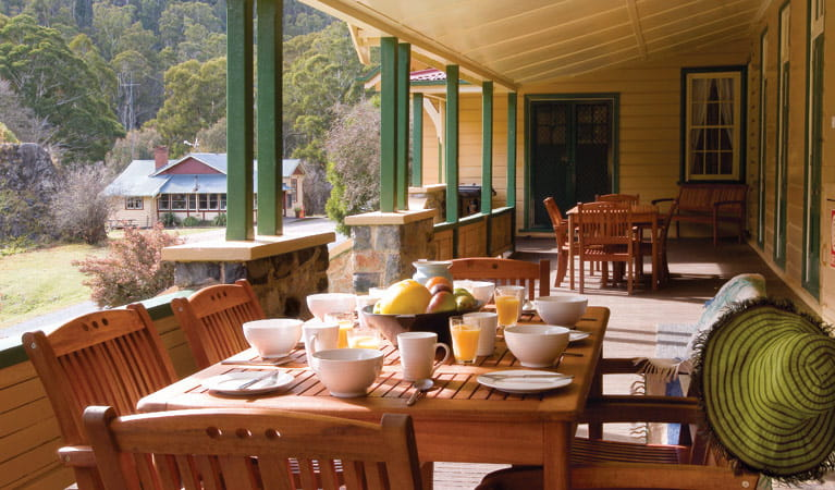 Breakfast on the verandah at Yarrangobilly Caves House 1901 section, Kosciuszko National Park. Photo: Michael van Ewijk/OEH.
