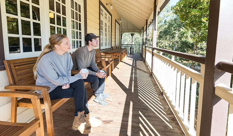 A couple on the balcony at Yarrangobilly Caves House 1917 section, Kosciuszko National Park. Photo: Boen Ferguson/OEH
