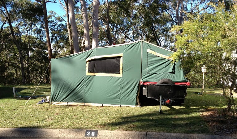 A large green camper trailer set up on a grassy area at Lane Cove Holiday Park - caravan park. Photo: Claire Franklin/OEH