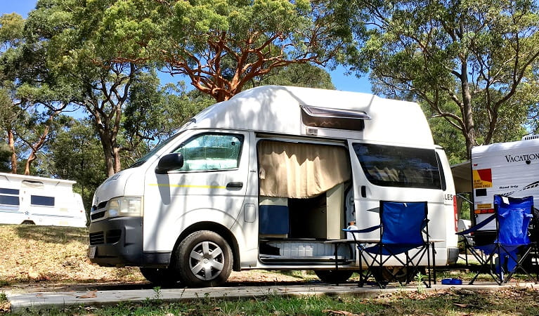 A campervan with two blue camper chairs at Lane Cove Holiday Park - caravan park, in Lane Cove National Park. Photo: Claire Franklin/OEH