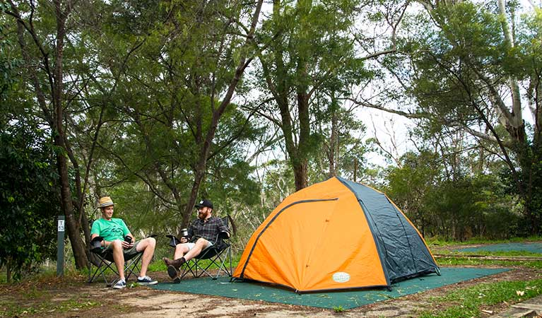 Two friends sitting next to their tent at Lane Cove Holiday Park - caravan park, in Lane Cove National Park. Photo: Caravel Content/OEH