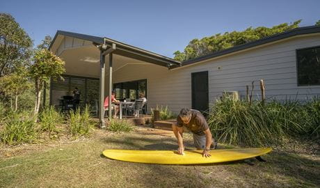 A man cleaning his surfboard on the grass nearby by the outdoor dining area at Plomer Beach House, Limeburners Creek National Park. Photo: John Spencer/OEH