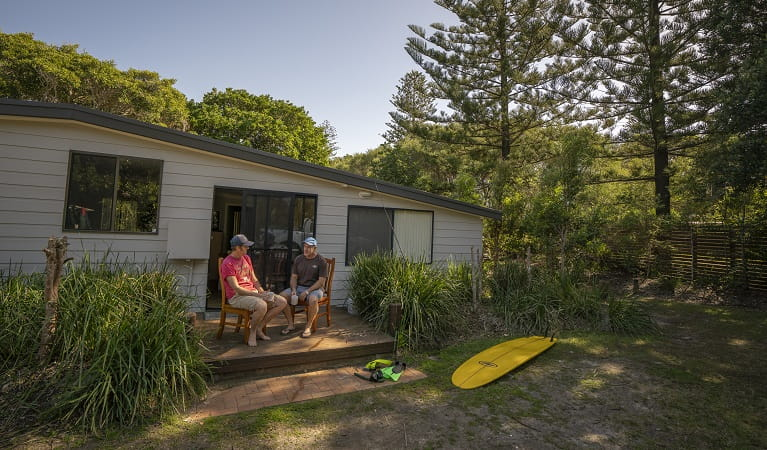 2 people sitting outside on the deck drinking a cup of coffee at Plomer Beach House, Limeburners Creek National Park. Photo: John Spencer/OEH