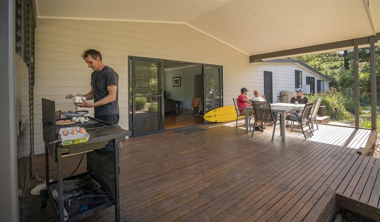 People in the outdoor dining area cooking breakfast on the barbecue and chatting at Plomer Beach House, Limeburners Creek National Park. Photo: John Spencer/OEH