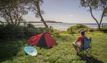 Man sitting beside his tent looking out at the ocean, at Limeburners Creek National Park. Photo: John Spencer/OEH
