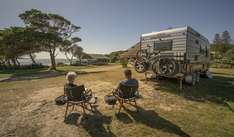 2 people sitting down beside their campervan looking out at the ocean at Point Plomer campground, Limeburners Creek National Park. Photo: John Spencer/OEH