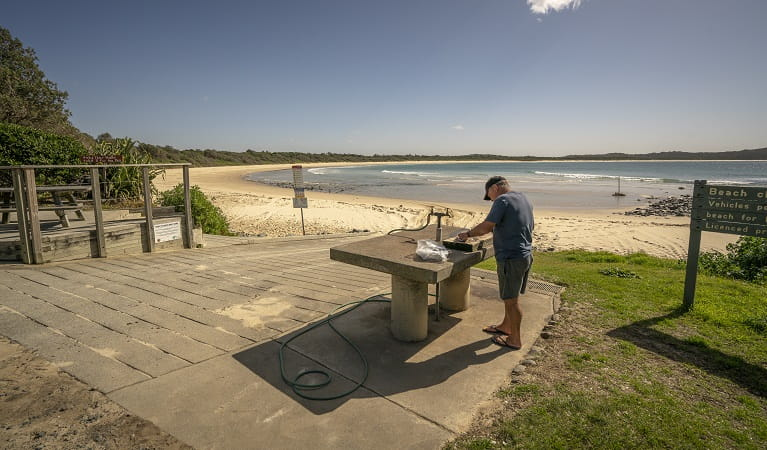 A fisherman cleaning his fish on a bench nearby the beach at Point Plomer campground, Limeburners Creek National Park. Photo: John Spencer/OEH