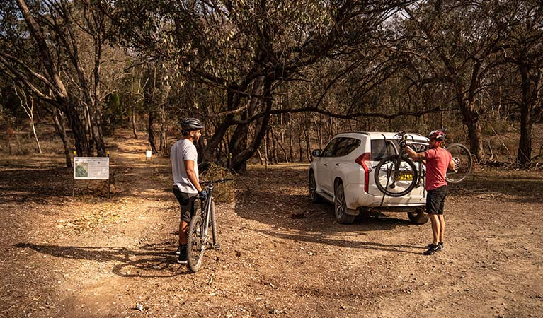 Two men take bikes off the back of a car at the start of a multi-use track in Livingstone National Park. Photo: Robert Mulally/DPIE