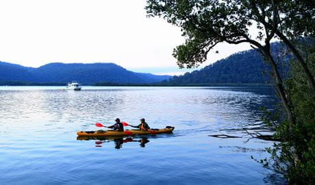 Hawkesbury River scene of 2 kayakers in a double kayak, with a river boat in the distance.  Photo: Rosie Nicolai/DPIE