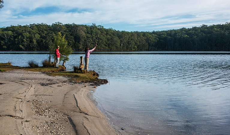 A man and a woman fishing on the shores of Burrill Lake in Meroo National Park. Photo: Michael Van Ewijk/DPIE