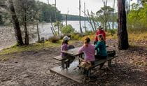 Group of 4 people at a picnic table in bushland setting next to Burrill Lake. Photo: Michael Van Ewijk/DPIE
