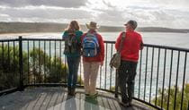 Bushwalkers looking along the coastline at Meroo Head Lookout, Meroo National Park. Photo: Michael van Ewijk/OEH