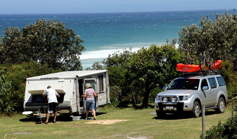 Campers with their camper trailer at Gillards campground, Mimosa Rocks National Park. Photo: John Yurasek/DPIE