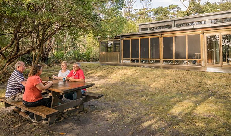 Visitors at a picnic table outside Myer House in Mimosa Rocks National Park. Photo: OEH/John Spencer