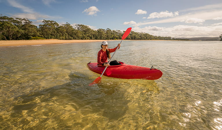 Woman in kayak at Bithry Inlet, at the mouth of Wapengo Lake in Mimosa Rocks National Park. Photo: OEH/John Spencer