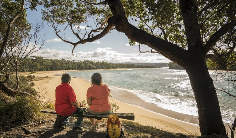 2 people sitting on a bench seat looking out the Bithry Inlet, mouth of the Wapengo Lake in Mimosa Rocks National Park. Photo: John Spencer/OEH