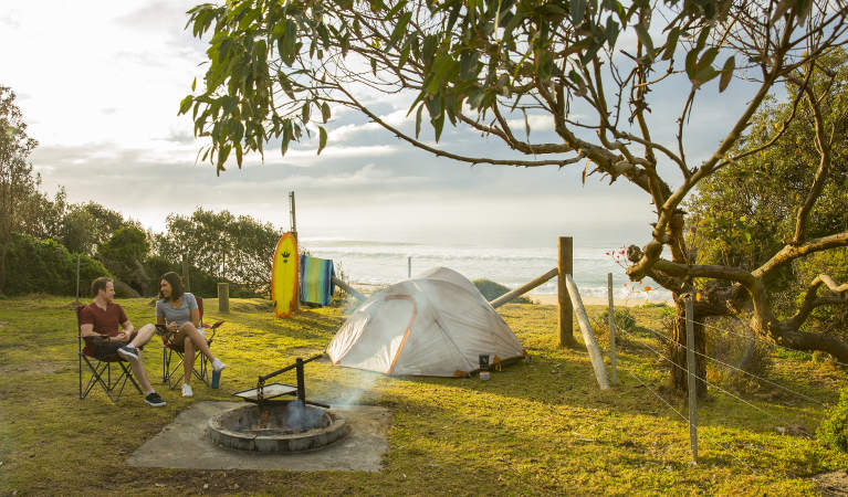 A couple relaxes beside the campfire at Gillards campground in Mimosa Rocks National Park. Photo: Tim Clark/DNSW