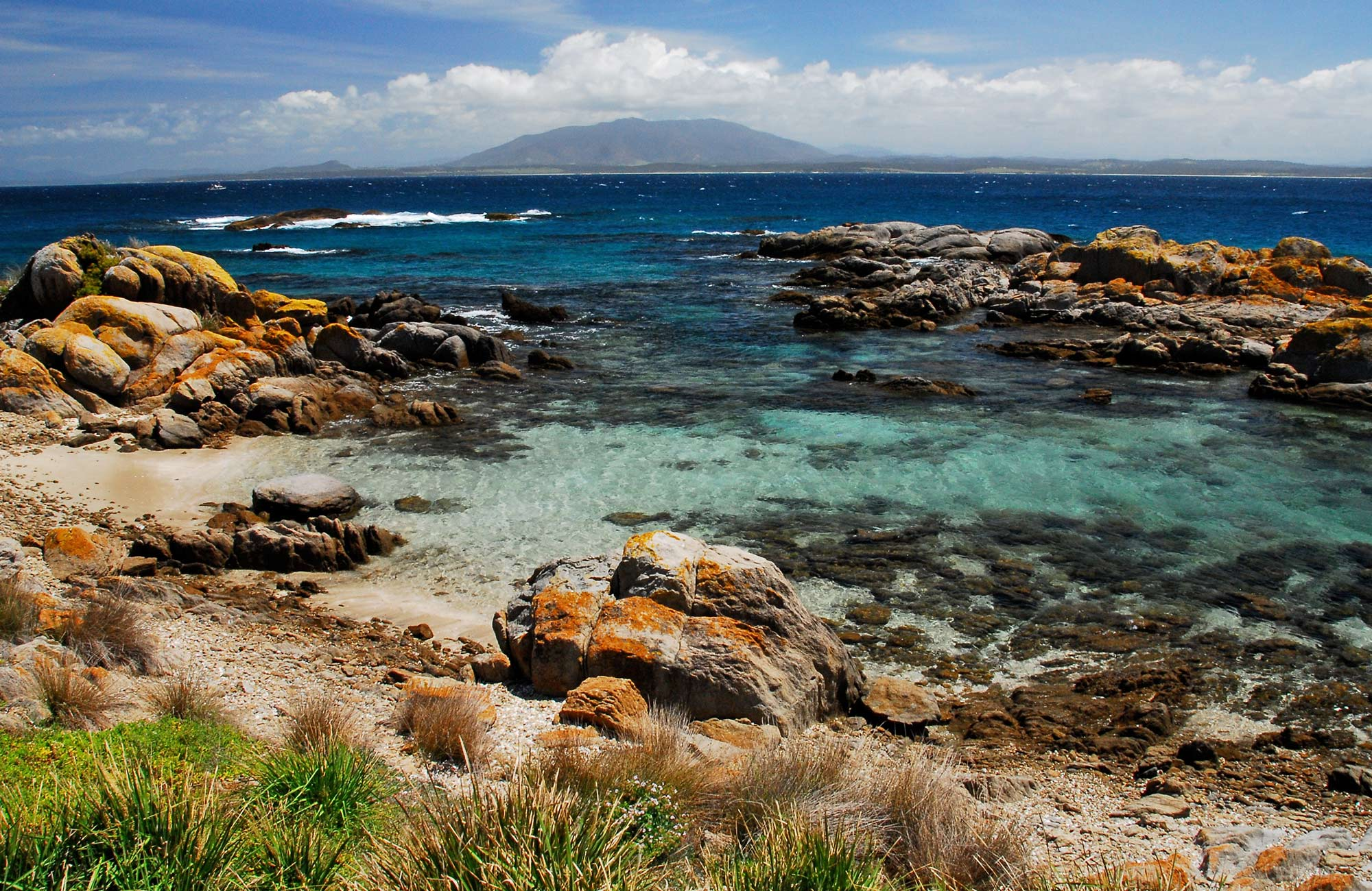Red rocks and aqua water on Montague Island foreshore with views across to Gulaga. Photo: Stuart Cohen/OEH