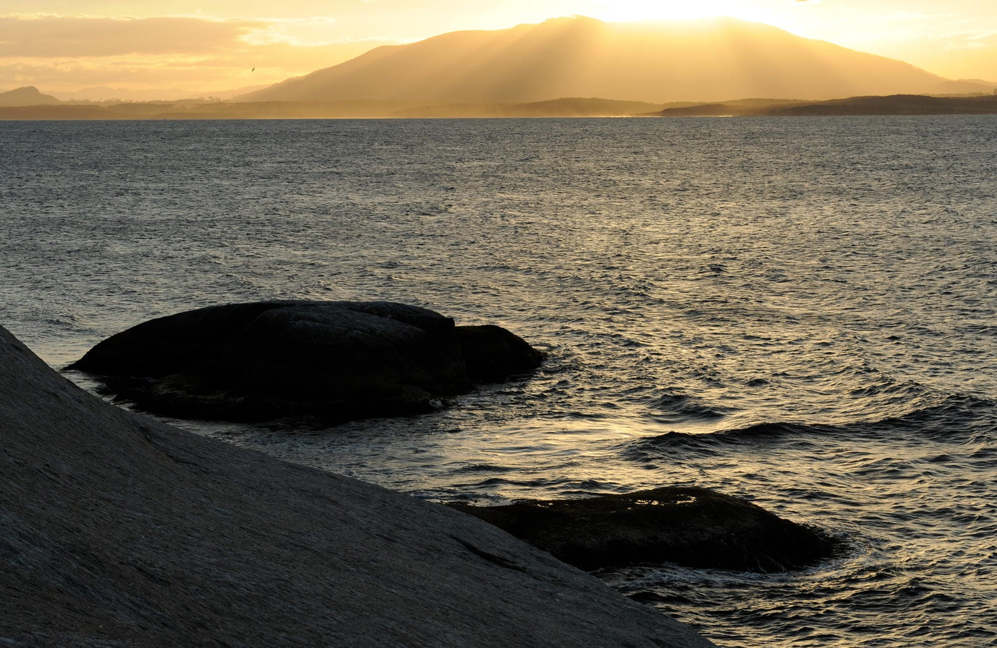 View from Montague Island across the sea as the sun sets behind Gulaga, near Narooma. Photo: Stuart Cohen/OEH