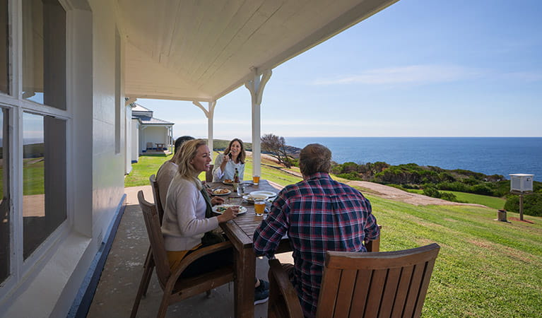 2 men and 2 women lunch at a table on the verandah outside Montague Island Head Lighthouse Keepers Cottage. Photo: Daniel Tran/OEH