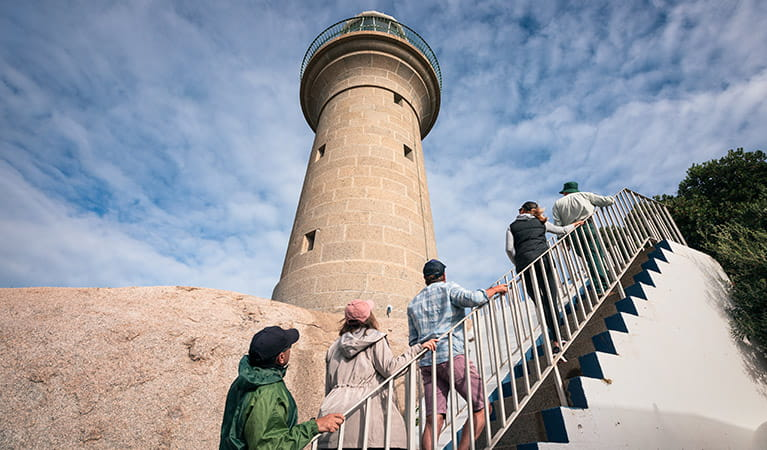 Visitors walk up stairs to the bottom of Montague Island Lighthouse. Photo: Daniel Tran/OEH